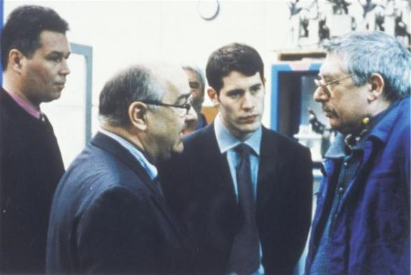 The son (second right) watches as the boss talks to his father on the shop floor.