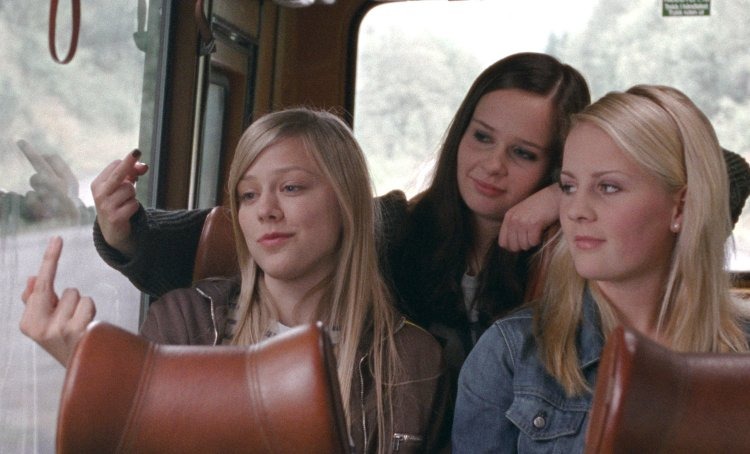 from the left: Alma (Helene Bergsholm), Sara (Malin Bjorhovde) and Ingrid (Beate Stofring) give the finger to the small town's nameboard.