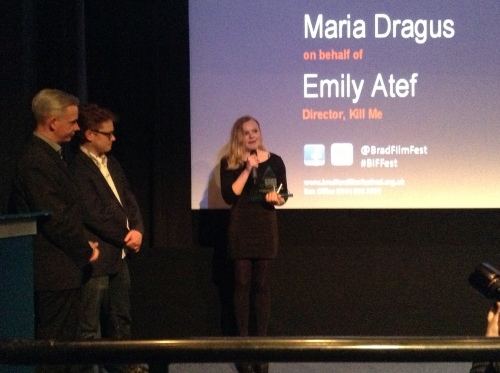 Maria Dragas, star of 'Kill Me' speaking after receiving the European Features award on behalf of Emily Latef – watched by Tom Vincent and Neil Young, Festival Directors.