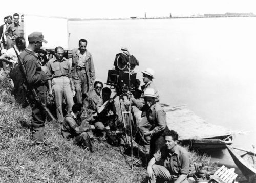 Roberto Rossellini (standing beneath the lighting reflector) on location in the Po valley for Paisa.