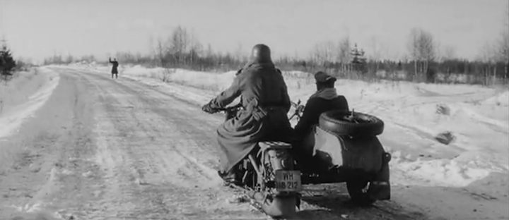 The distant figure of Lazarev in German battledress stops a a motorcycle and sidecar in an ambush.