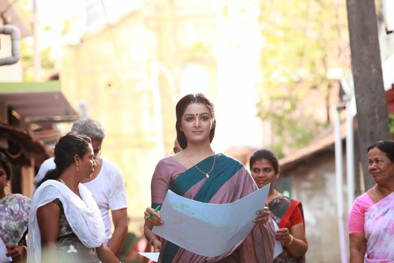 A woman in a pink-teal sari has a large paper unfolded in her hands. She looks ahead as she navigates through a crowd.