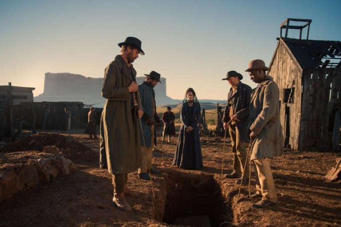 (Eva Green) watches as her husband is buried in the remote town. The mesa behind her in the distance is a CGI addition to the South African landscape.