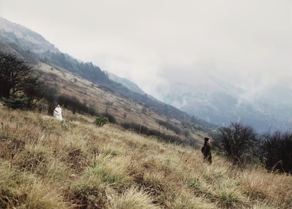 A long-shot composition with action in the foreground and misty mountains in the background
