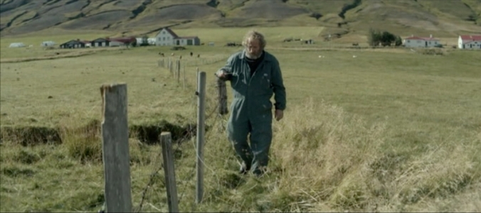 Gummi (Sigurður Sigurjónsson) checks the fence between the two properties – the houses are shown in the background